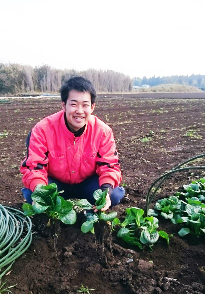 小松菜を手にする生産者の加藤さん