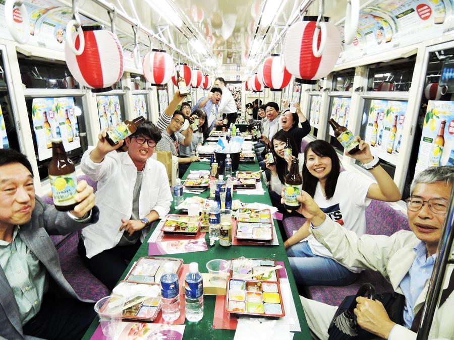 チューハイ列車車内、乾杯する参加者