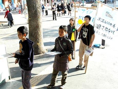調布駅南口広場で京王電鉄の6000系車両の存続を求めて署名活動をする小学生