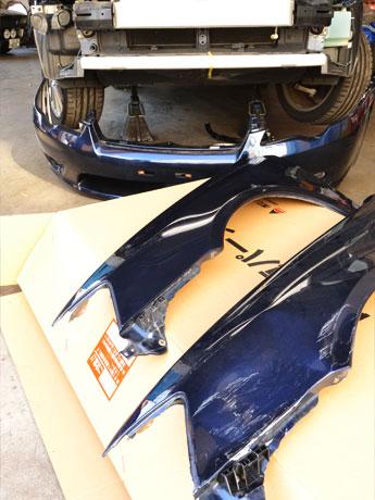 自動車修理でリサイクルパーツ利用増。手前が大きく傷がついたパーツ。奥がリサイクルパーツ