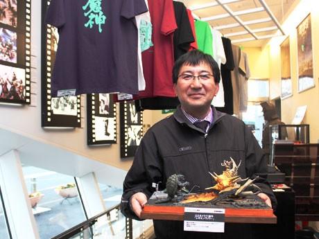 ショップ担当の吉村健治さん。雑誌企画用のジオラマを手に