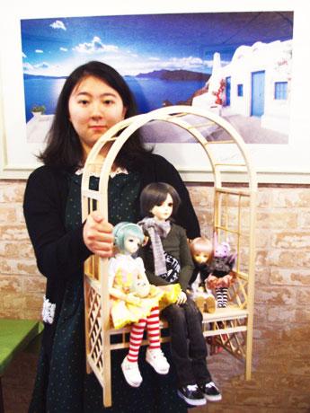 仙川でドール撮影会を開催。写真は企画者の麻美さん。店主の藤原さんと共同制作した撮影用ベンチをもって