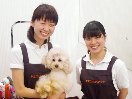 愛犬で、お店の看板犬の「ティロちゃん」を抱える、ショップリーダーの嵐田日都美さん(写真左)。嵐田さんはいつも愛犬を連れて出勤。