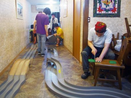 参加者によるコース作りの様子。障害物を手作りしている店主の藤原さん(写真右)。