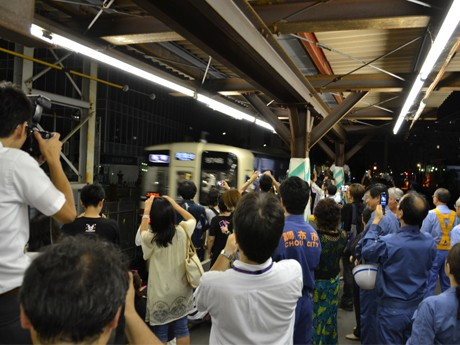 調布の地上駅の最終電車を見送る人々