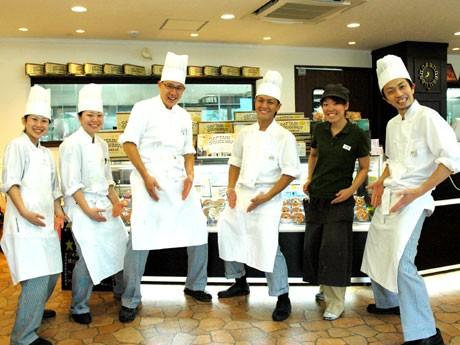 洋菓子店「パティスリーアノ-」のスタッフ。商品の狛江コルネ「コマネ」にちなんで、国民的ギャグ「コマネチ」のポーズで撮影。
