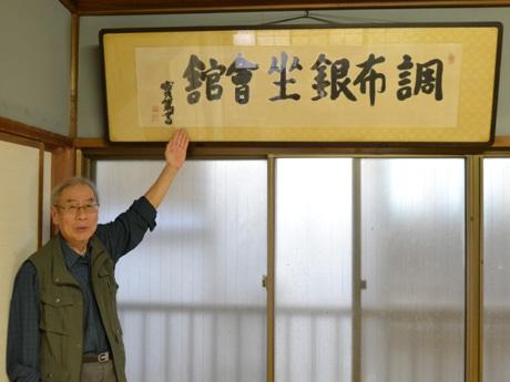 実篤直筆と判断された調布銀座会館の書。左は同商店会の理事長を務める齋藤行雄さん
