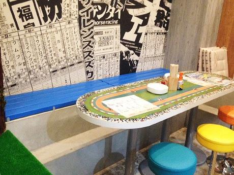 壁面には競馬新聞誌面の拡大版をプリント、テーブル席のベンチは競馬場と同様のものを採用