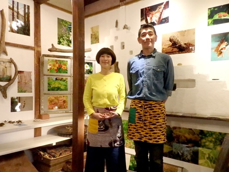 店主の笠原夫妻。庭で撮影した写真が展示された店内ギャラリーで