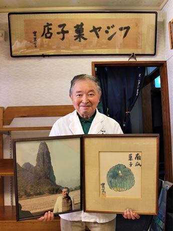 「藤屋」2代目店主斉藤庄一郎さん 実篤氏直筆のカボチャの絵と旧店名の看板、先代の写真とともに