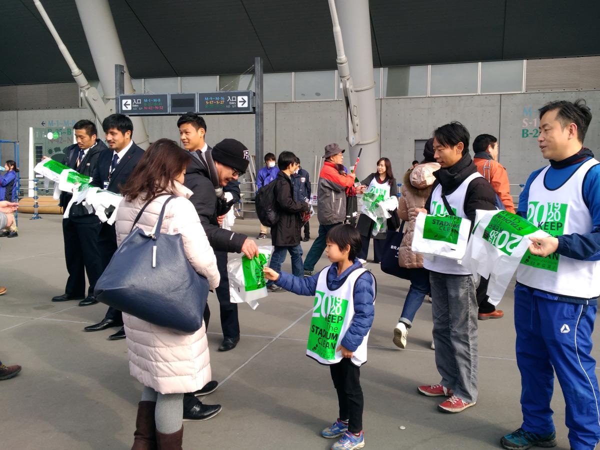 東芝府中の選手や市民ボランティアがごみ袋を配布する様子