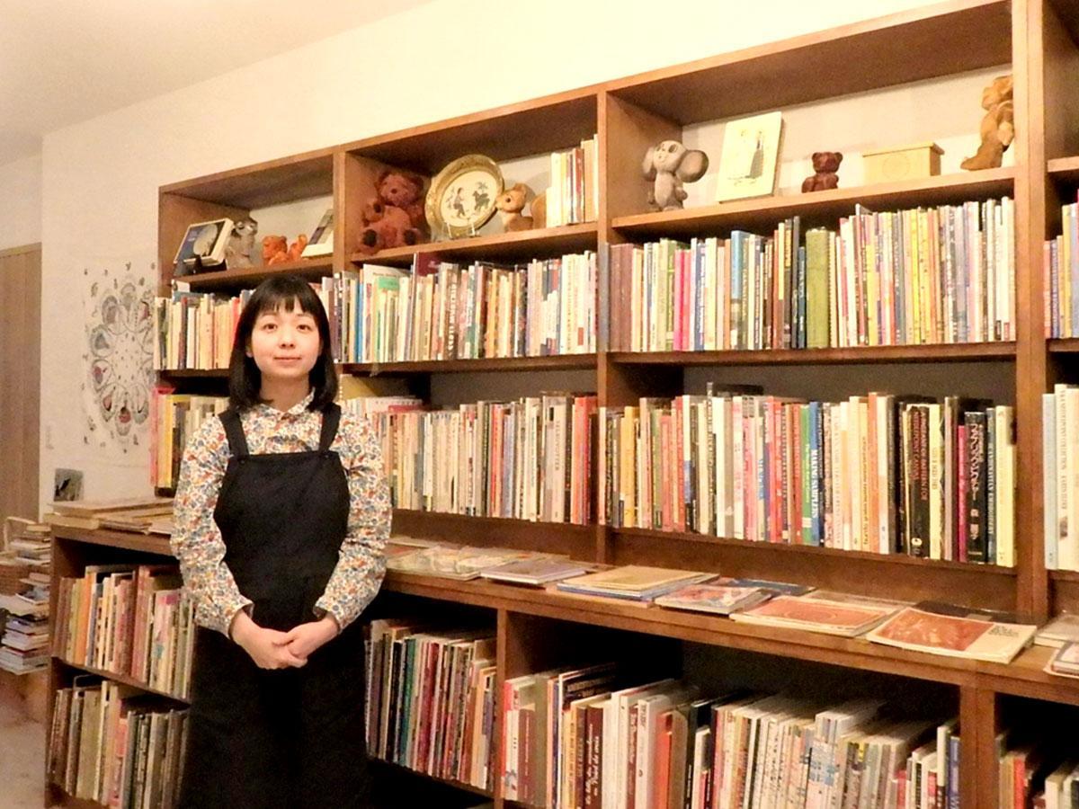 「folklora(フォルクローラ」店主の石井さん、古書が並ぶ書棚の前で