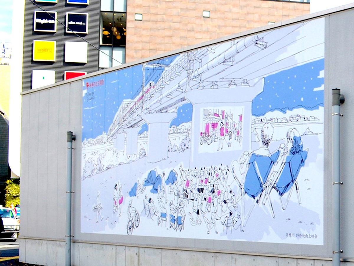 調布駅広場口の地上部建物の壁面に描かれたねぶくろシネマ「多摩川映画上映会」