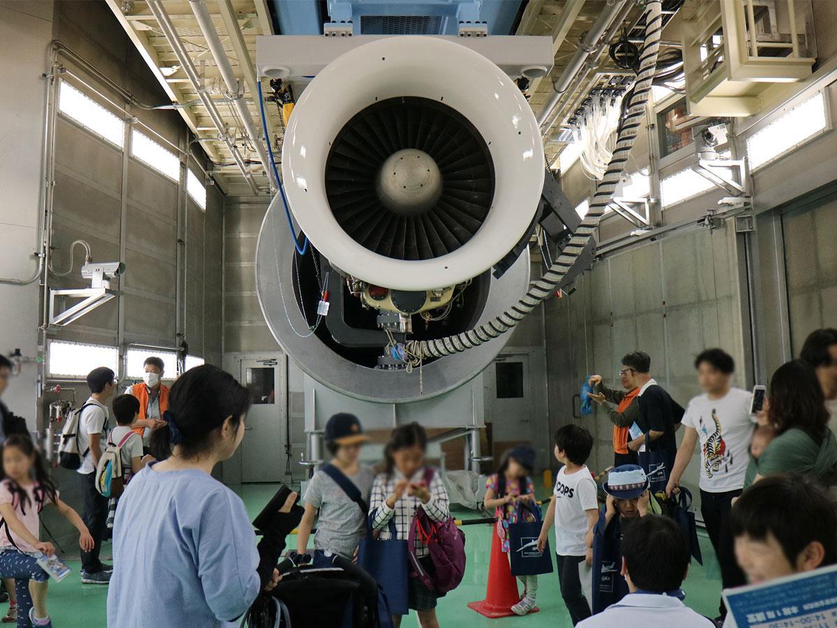 第1会場で、普段は見られない大きなファンジェットエンジン試験設備を見学する大勢の来場者(昨年の様子)