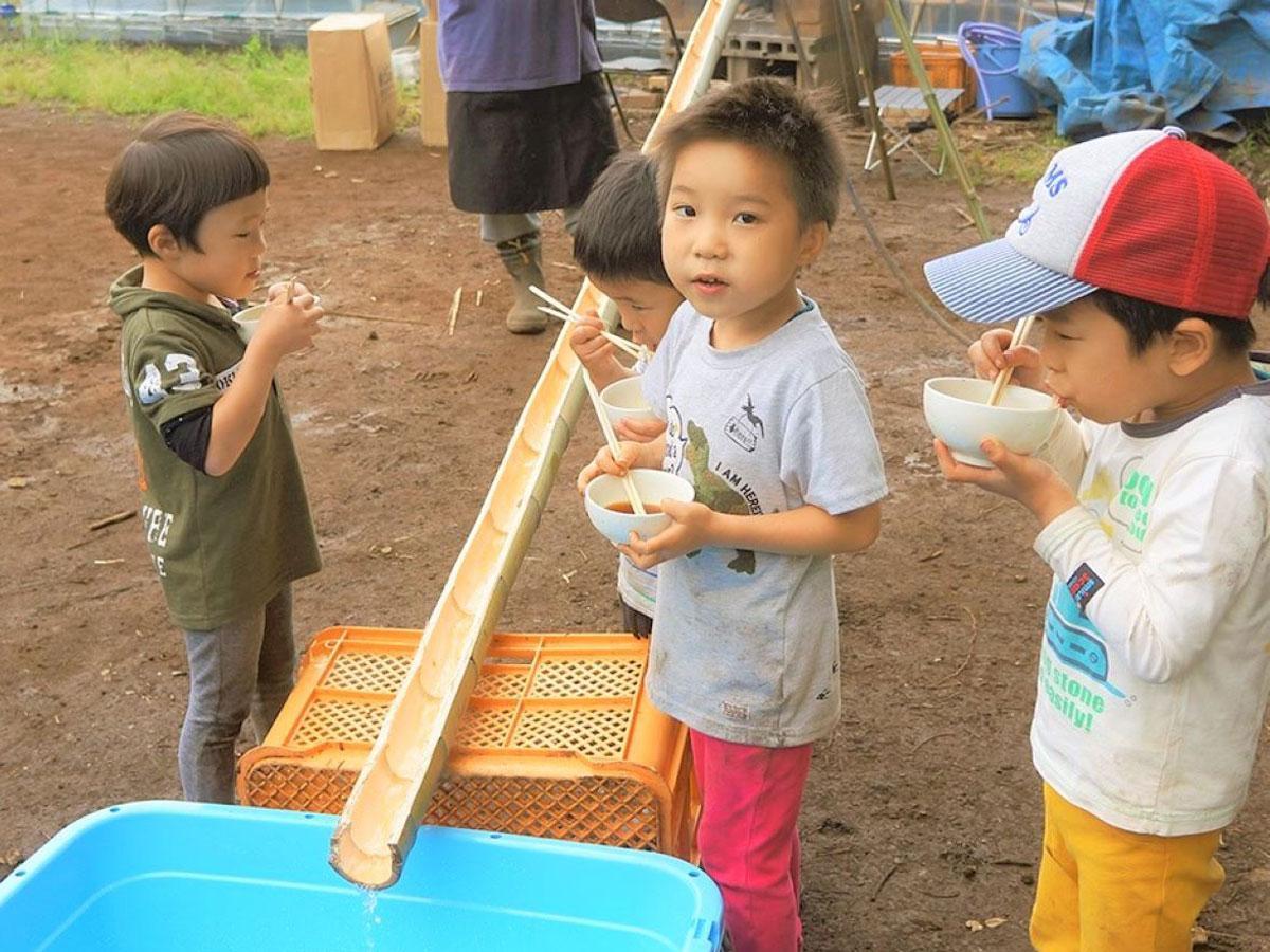 「山内ぶどう園」の手作り竹レーンで流しそうめんを楽しむ子どもたち