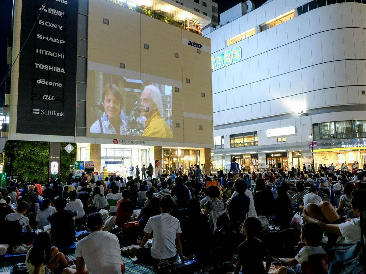 調布発祥の野外映画イベント「ねぶくろシネマ」。トリエ京王調布B館の壁面を使って開催する様子