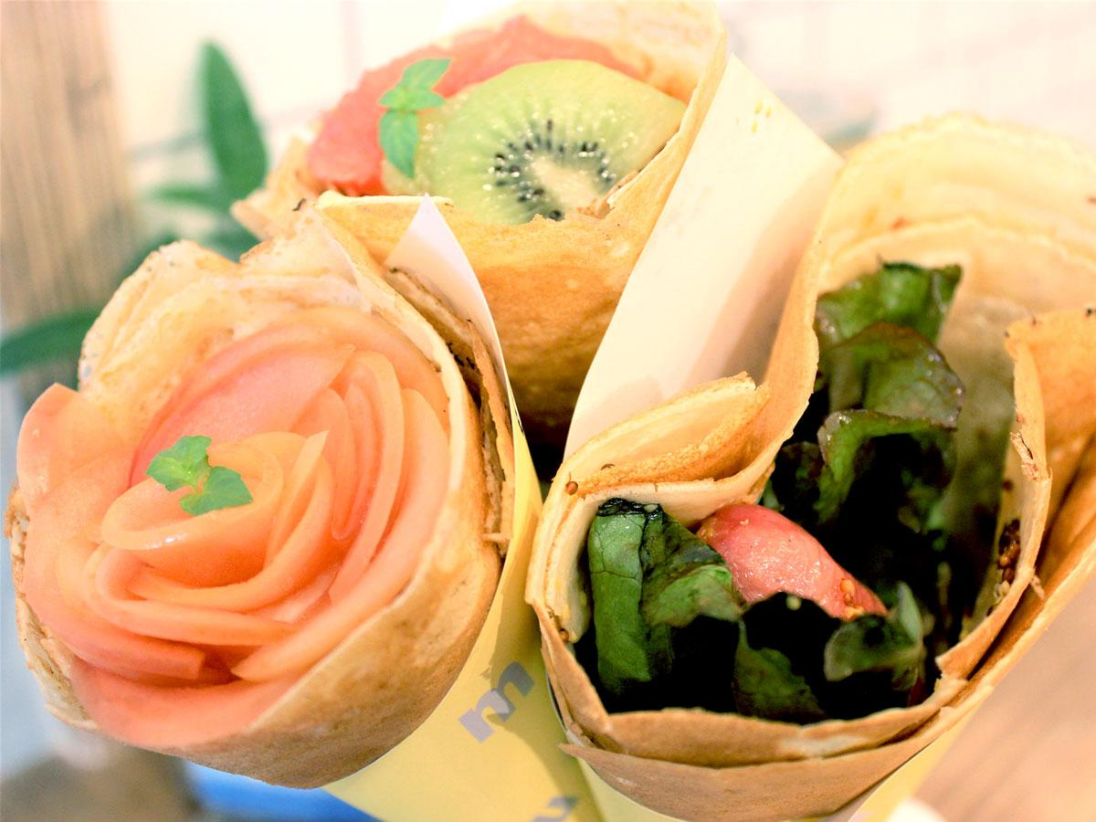 「mococo CREPE」の林檎のコンポートとムースフロマージュのクレープ(左)大きなフランクと粒マスタードのクレープ(右)キウイとグレフルとムースフロマージュのクレープ(奧)