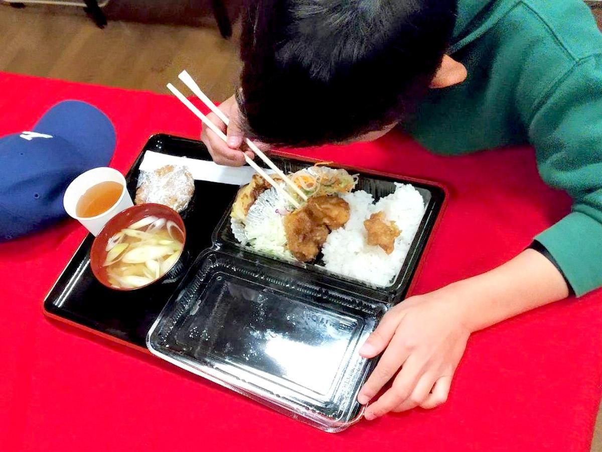 3月5日開催の様子、プラスチック容器で用意された食事を食べる男児