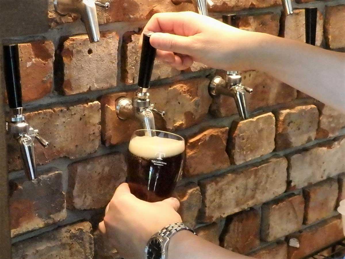 こだわったというレンガの壁の「タップ」から注がれるクラフトビール