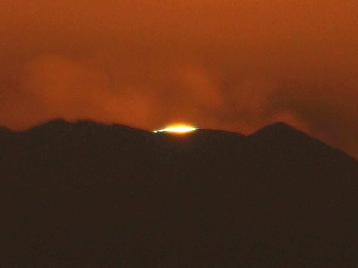 富士山頂に太陽が沈む直前の「グリーンフラッシュ」。細くなった太陽光の両端が緑色に見える
