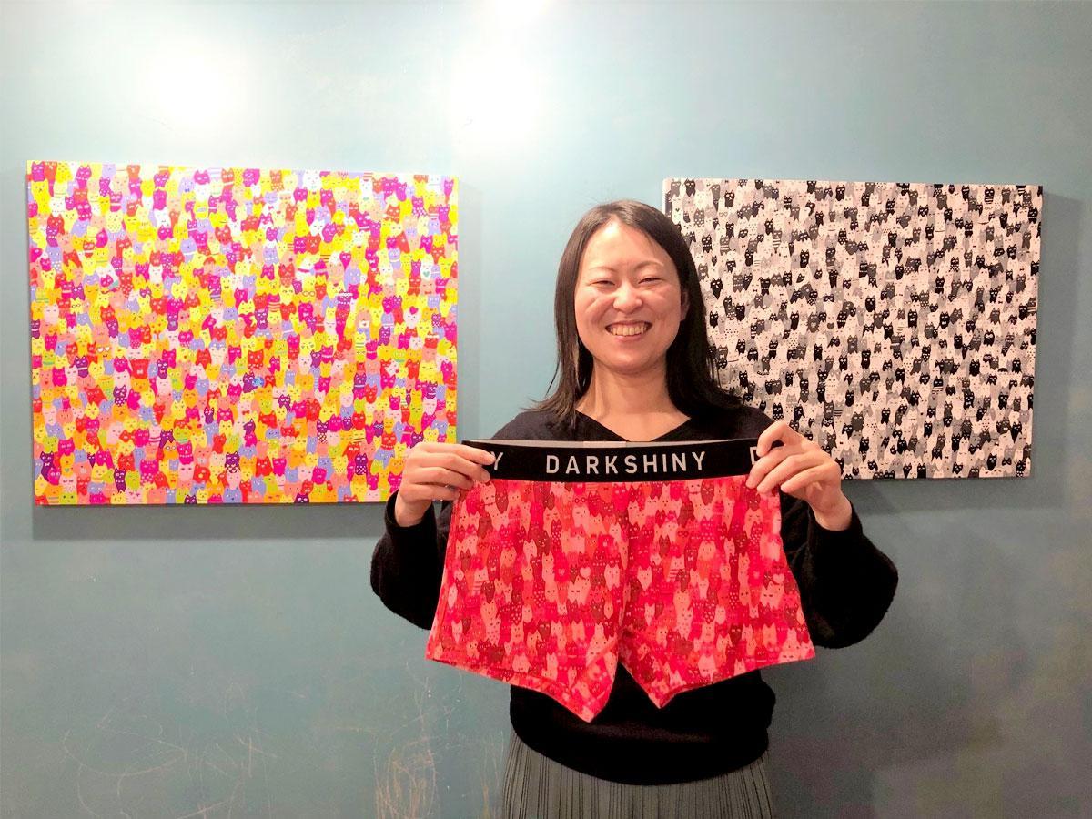 イラストレーターの佐山愛さん、手には「DARK SHINY」のコラボパンツ「ねこだらけ(レッド)」、背景は「ねこだらけ」原画