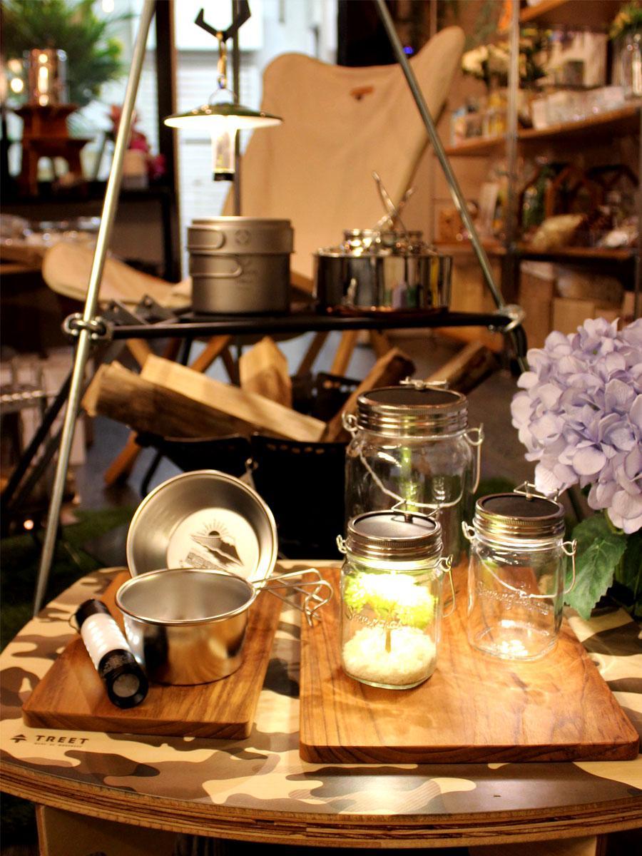 「Kekke Works」オリジナルブランドのシェラカップやとキャンプ用品・「カロハル」の看板商品ソネングラスと造花。店内には数多くの商品が並ぶ