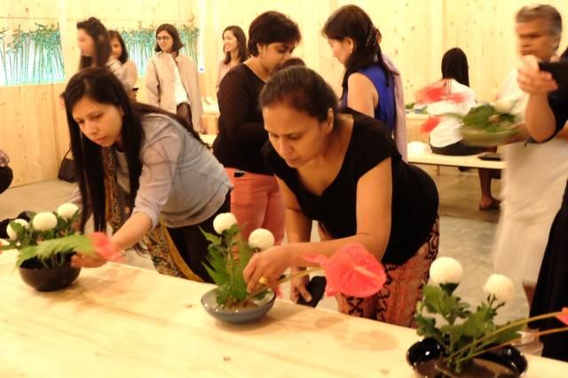 真剣な表情で花を生ける参加者たち