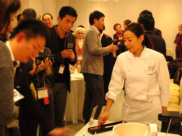 来場者に商品の特徴を説明する秋元さん(右)