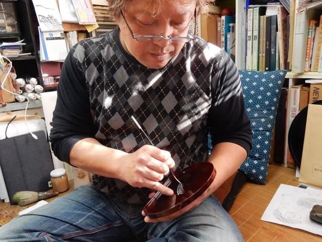 鮮やかな手つきで絵を描く昌敏さん。「右手の位置を固定したまま、左手だけを動かすのがこつ」という