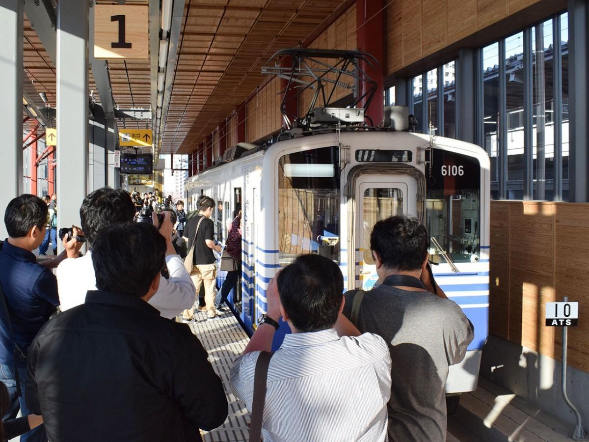 一番列車の入線をカメラに納める鉄道ファン