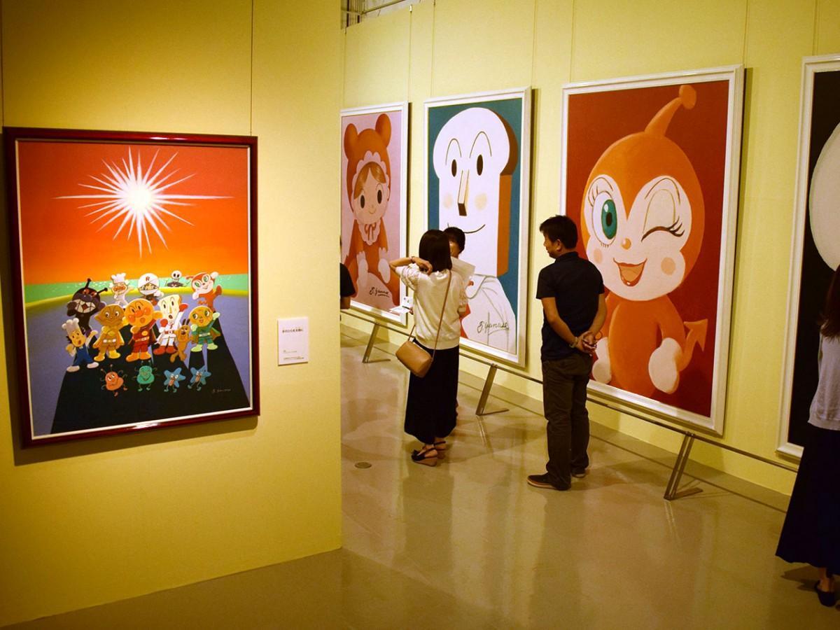 50号サイズのアクリル画「手のひらを太陽に」(左)など、大型作品に見入る来館者