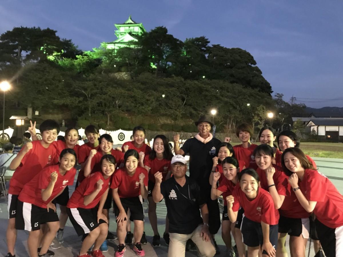 赤色の応援Tシャツを着けた福井丸岡RUCKのメンバー。奥はライトアップされた丸岡城(坂井市)