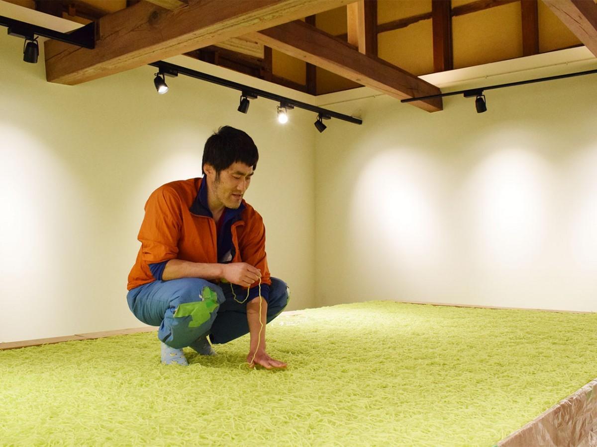 制作に取り組む前田さん。全ての毛糸の両端を結び、最終的に一本の輪にするという