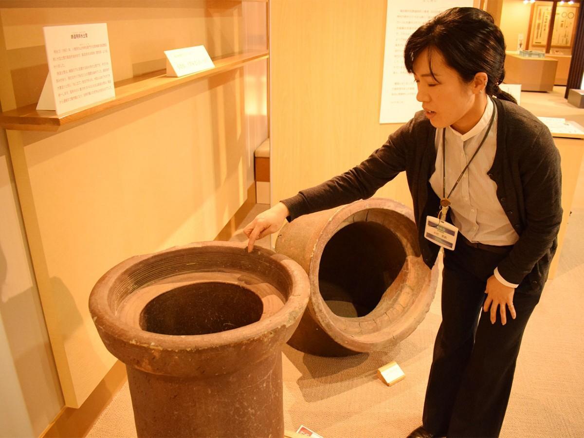 明治中期に作られた鉄道土管を解説する木村さん。土管の重量は約70キロという