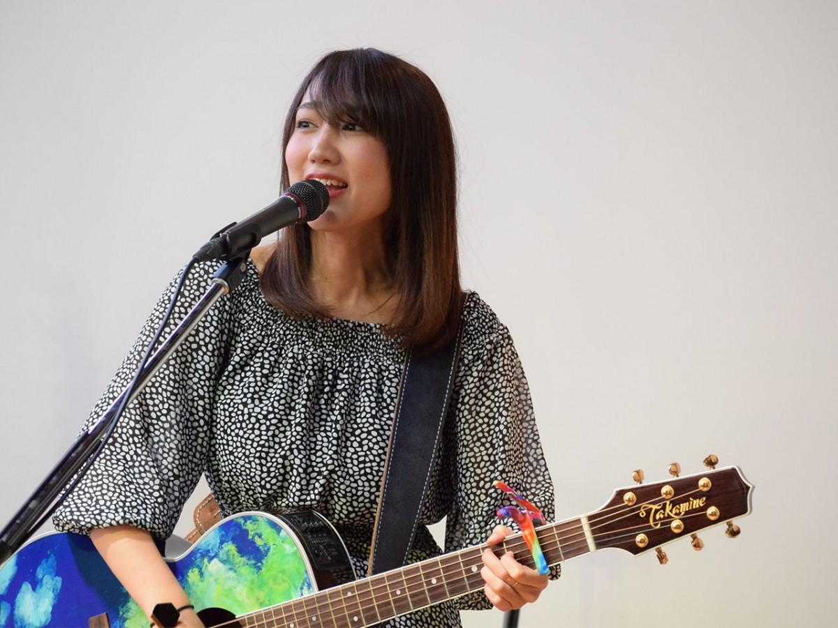 カラフルなカポタストを付けた「地球ギター」を手に出演したせりかなさん