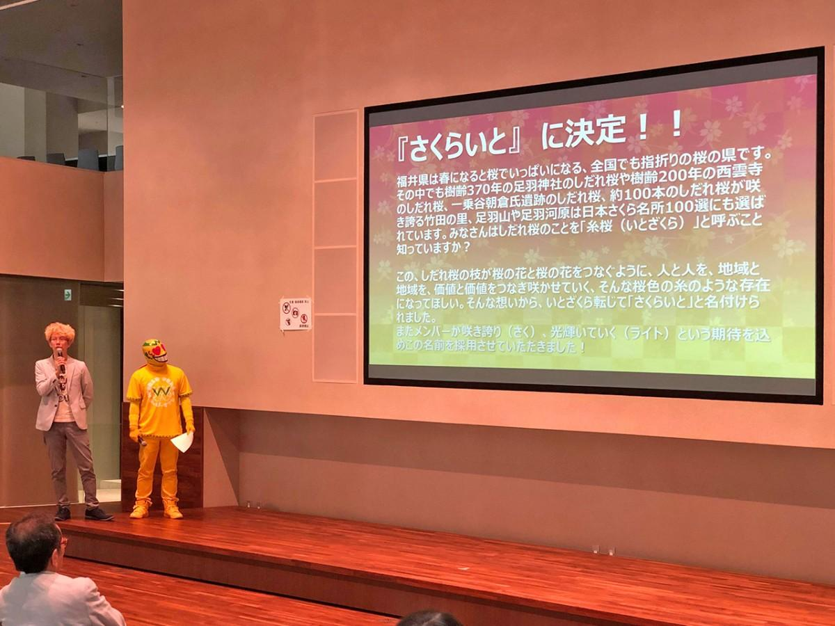 グループ名の由来を解説する川縁さん(左)と、MCを務めた福井のご当地ヒーロー「はっぴーすマン」(右)