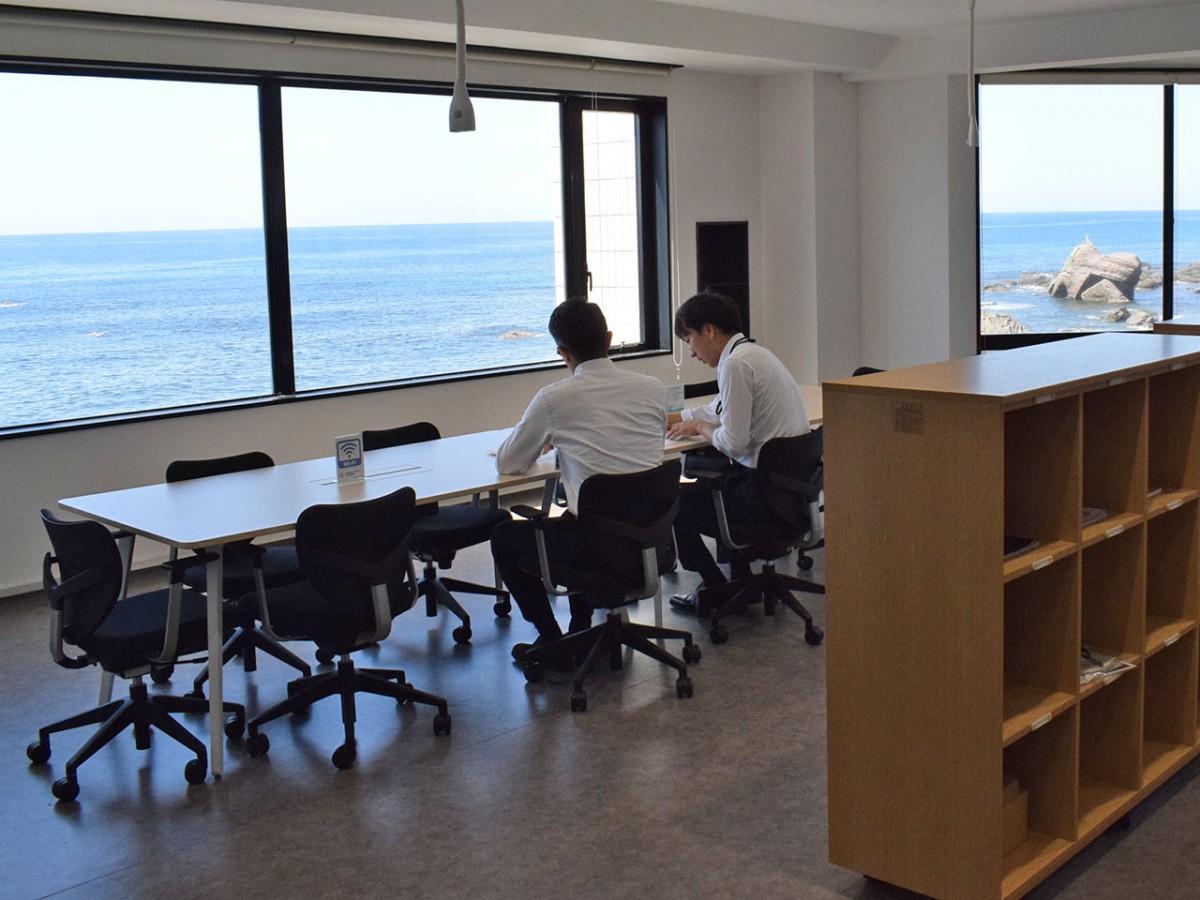 テーブル席で打ち合わせする利用者。窓の外には日本海の風景が広がる