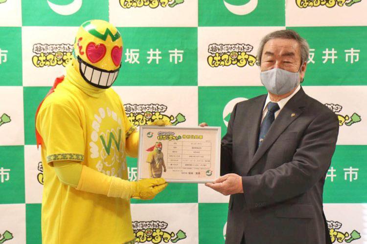 坂本憲男坂井市長(右)から特別住民票を受け取る「はっぴーすマン」(左)