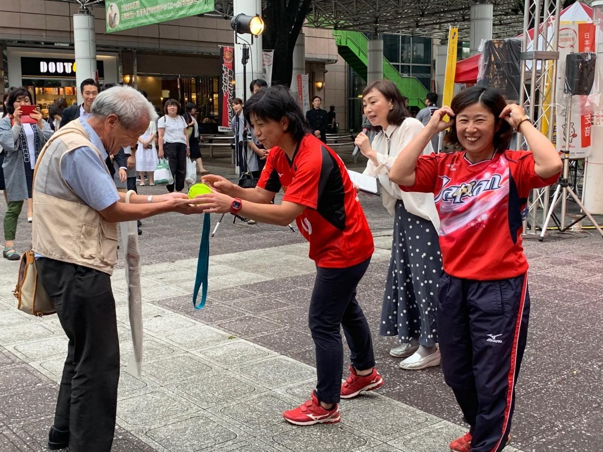 市民にメダルを渡すなどして交流したソフトボール元オリンピック選手の田本博子さん(右)と伊藤幸子さん(中央)