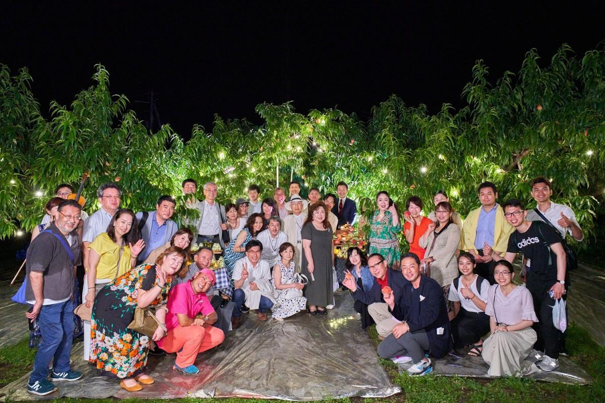 「夜の果樹園」で記念撮影する参加者たち