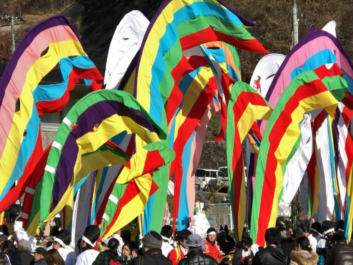 「木幡の幡祭り」で色とりどりの旗を担ぎ行進する参加者ら