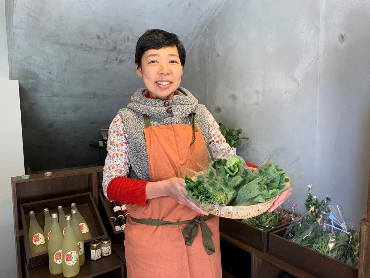 野菜を手にオープンをアピールする店主の佐藤宏美さん