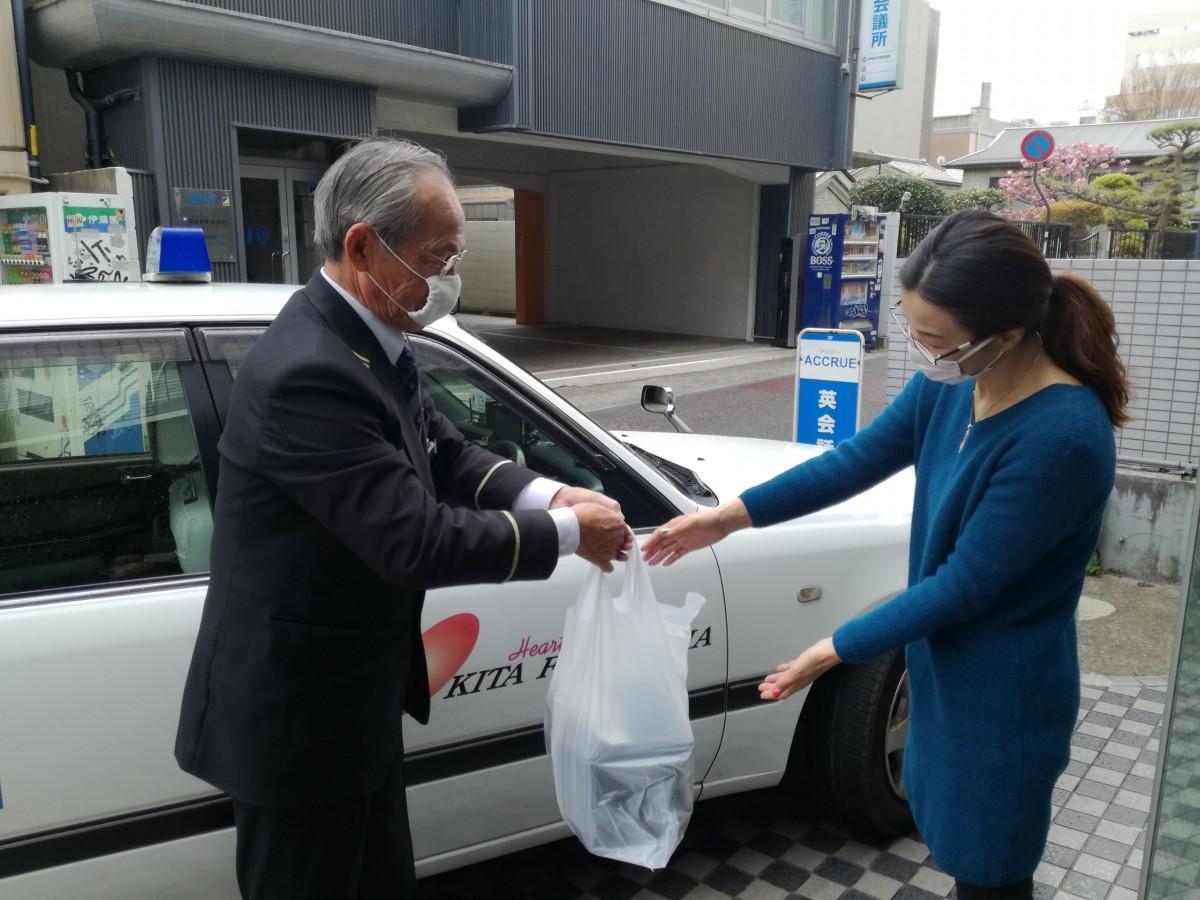 タクシードライバーから商品を受け取る利用者
