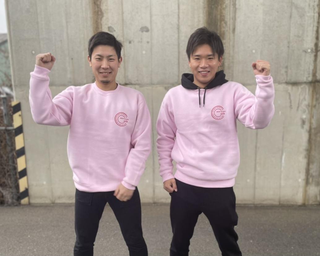 イメージカラーのピンクの制服で笑顔を見せる「EVO TO WIN(エボトゥウィン)」の伊藤仁哉さん(左)と鈴木翼さん(右)
