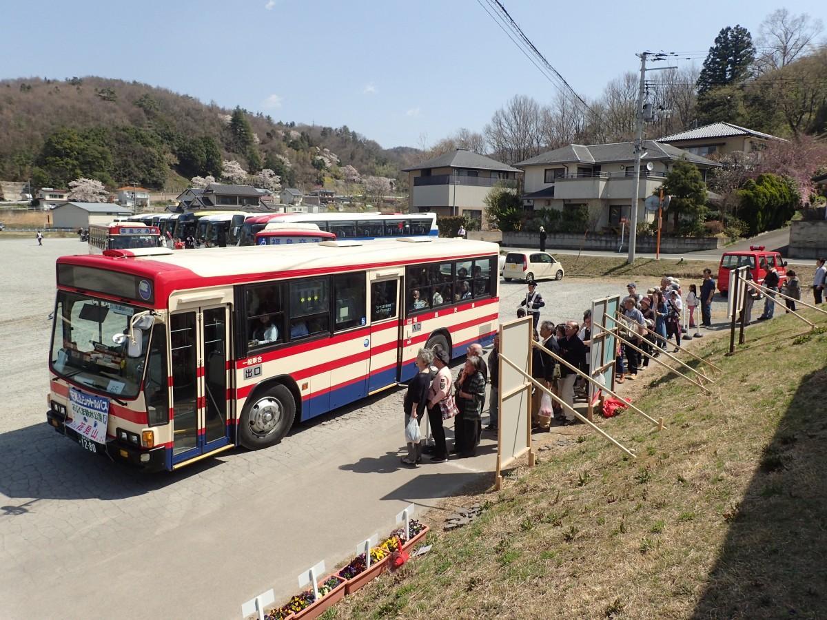 シャトルバス「花見山号」と、バスを利用するために列をつくる観光客ら(2017年撮影)