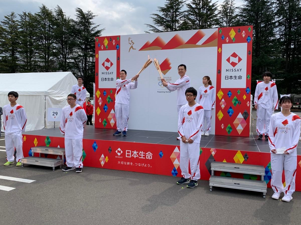 トーチキスをする聖火リレーランナーの神酒(みき)太郎さん(上段中央左)と櫻井英樹さん(上段中央右)
