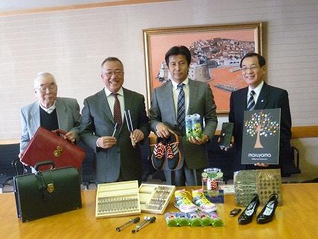 認定された商品を手にする4社の代表