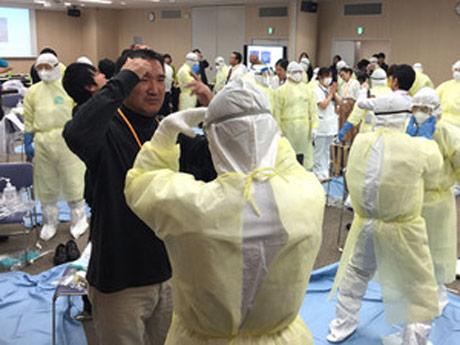 「PPE」とよばれる感染防護服の着脱を行う医師たち