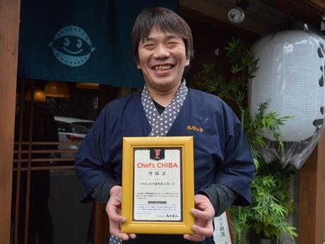 店の前で登録証を手にする店長の村山考志さん