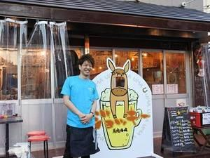 店長の野村さんと店のキャラクター「ジョッキー」の看板